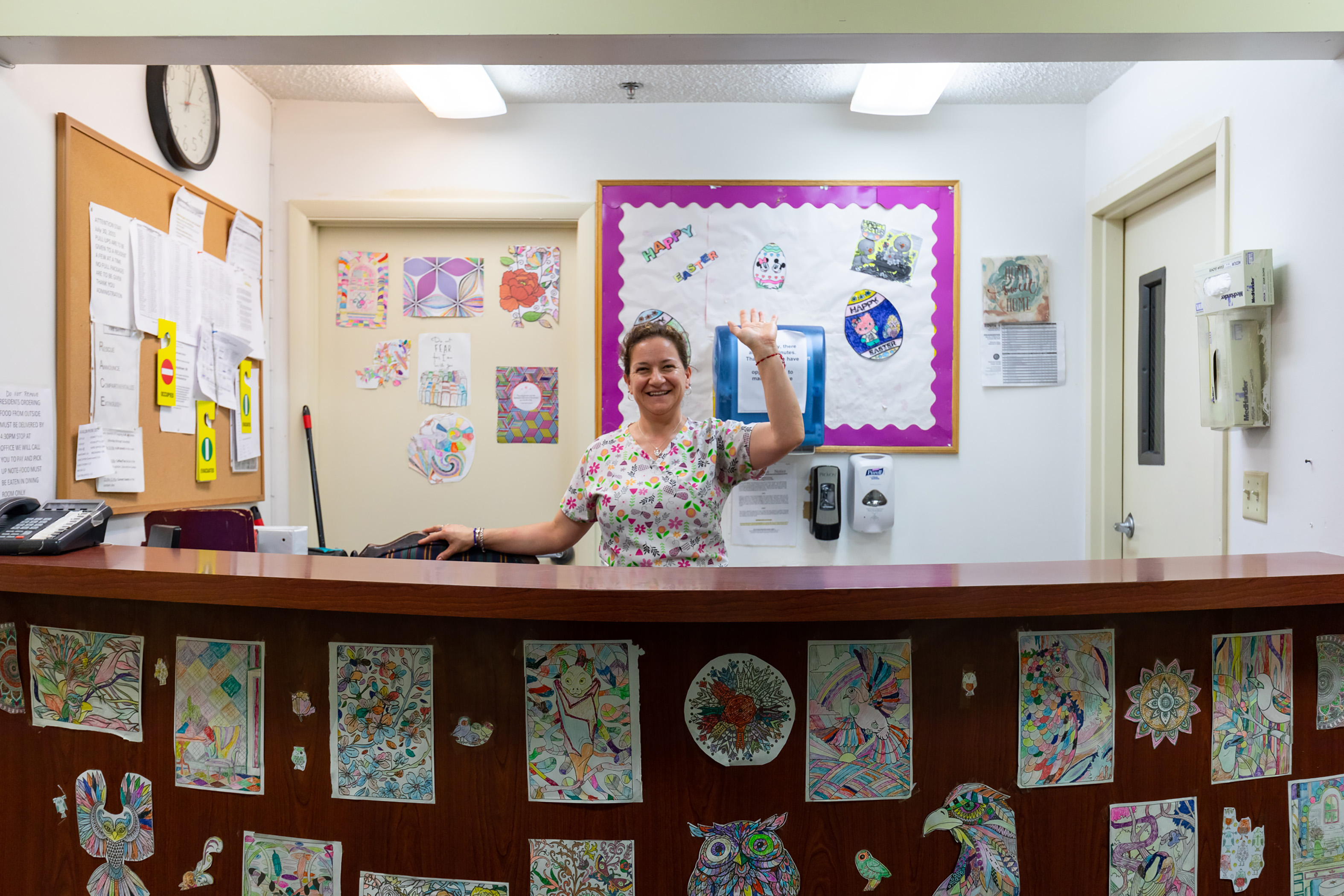 Photo of front desk receptionist waving hello