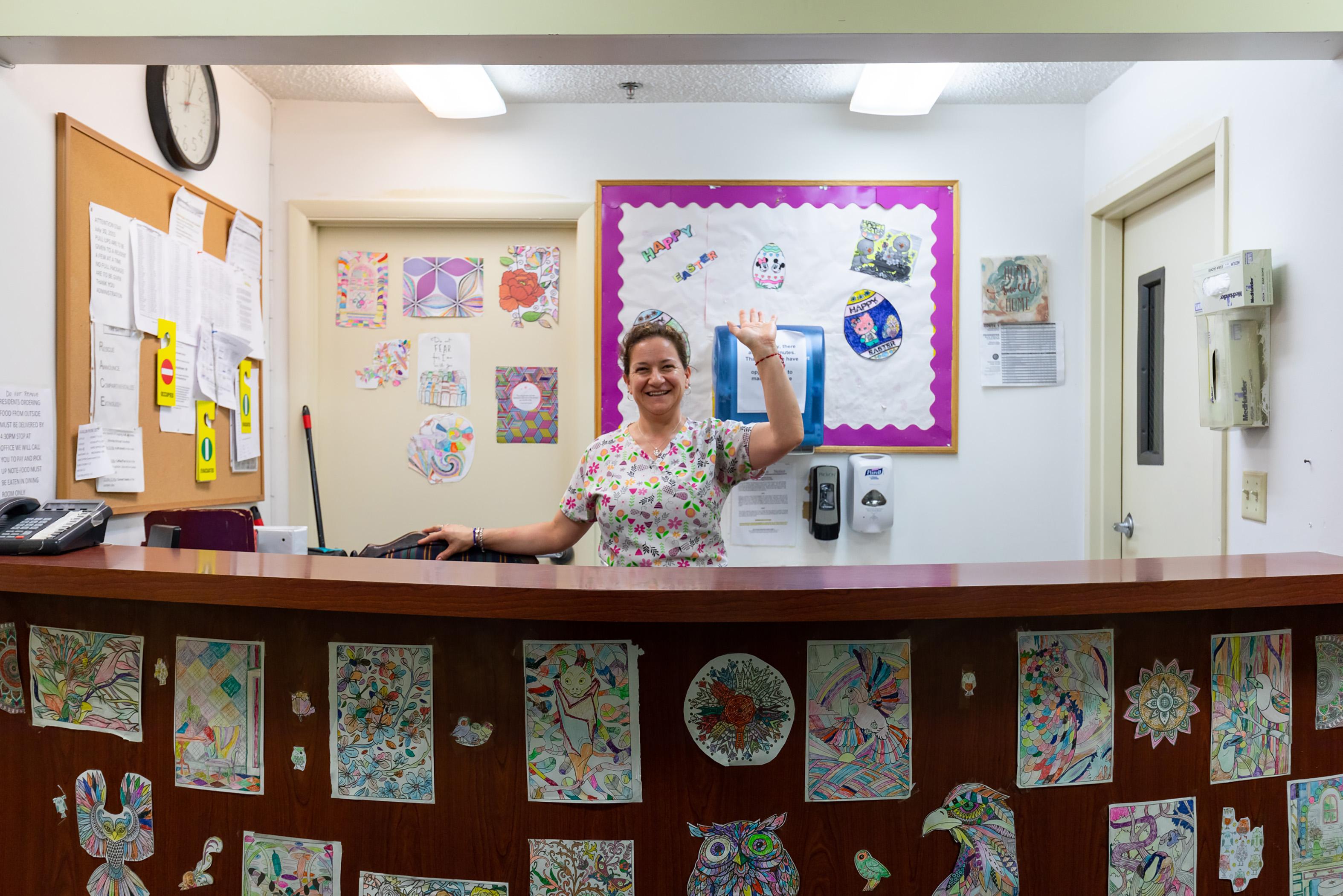 Photo of front desk receptionist waving hello